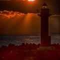 写真: 灯台と夕陽