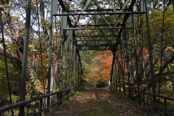 緑のアーチ橋の先にちらっと見える紅葉